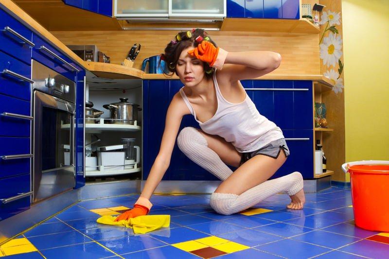 Женщина в бигуди моет пол на кухне